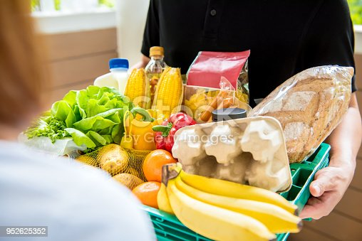 istock Delivery man delivering food to customer at home 952625352