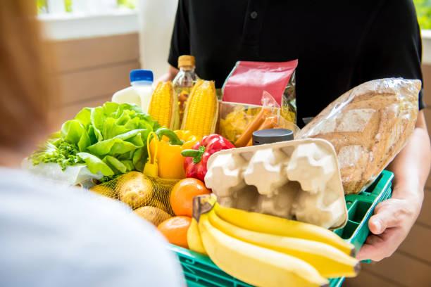 delivery man delivering food to customer at home - prodotti supermercato foto e immagini stock