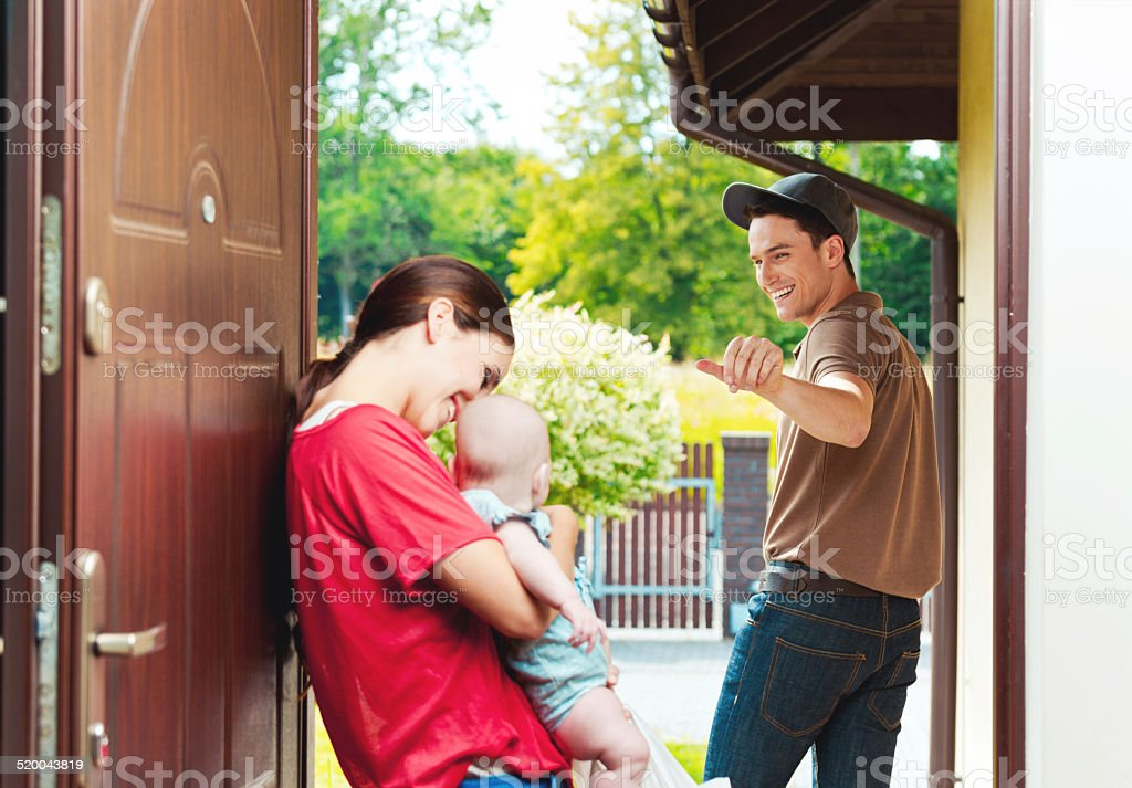 Delivery man delivering take away food for young woman Young mother standing at the door of the house, holding his little baby and take away food in hands while delivery man saying good bye. Adult Stock Photo