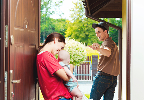 Delivery Man Delivering Take Away Food For Young Woman Stock Photo - Download Image Now