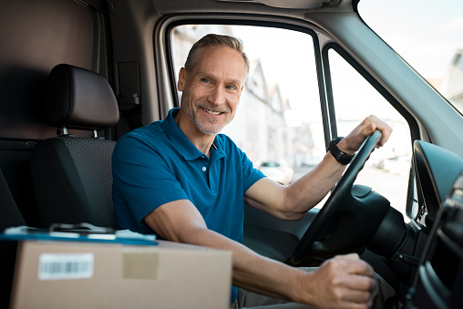 Delivery man driving van with packages on the front seat. Happy mature courier in truck. Portrait of confident express courier driving his delivery van.