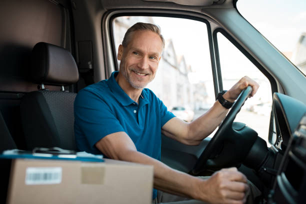 delivery man driving van - driver stock photos and pictures
