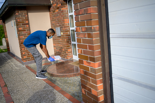 Delivery man dropping off pizza box at doorstep