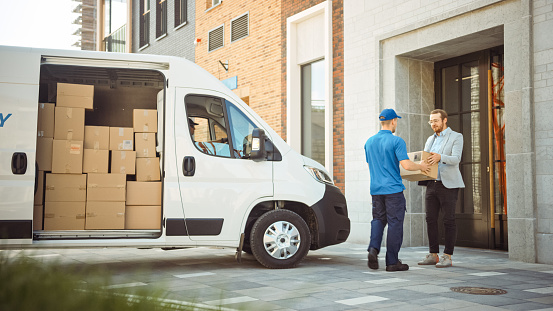 Delivery Man Gives Postal Package to a Business Customer, Who Signs Electronic Signature POD Device. In Stylish Modern Urban Office Area Courier Delivers Cardboard Box Parcel to a Man
