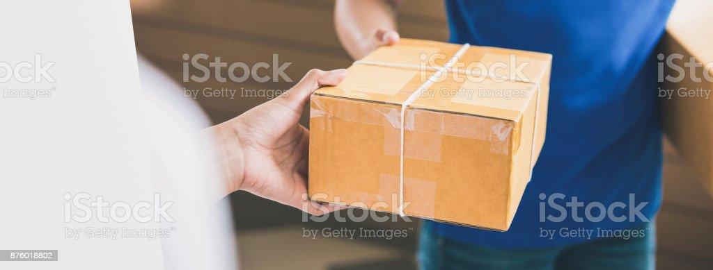 Bote ein Paket an eine Kundin übergeben – Foto