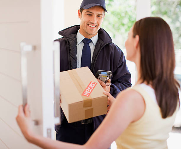 доставка человек, передачей box для женщина - postal worker стоковые фото и изображения