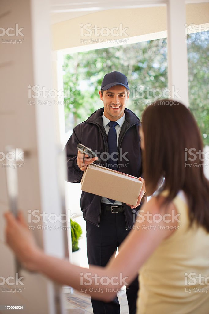 Delivery man handing box to woman royalty-free stock photo