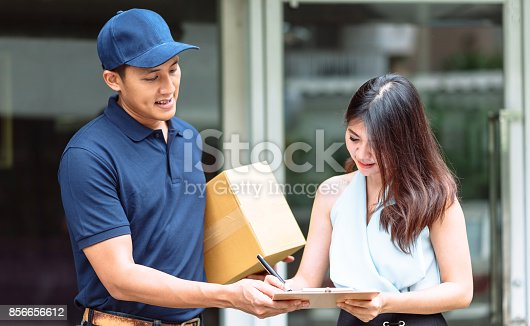istock delivery man holding a cardboard box while beautiful Asian woman putting signature 856656612