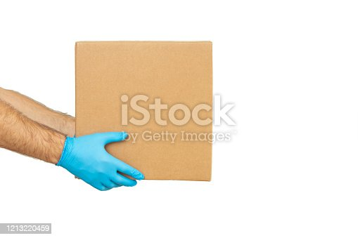 Delivery man holding cardboard boxes in medical rubber gloves / copy space. Fast and free Delivery transport . Online shopping and Express delivery