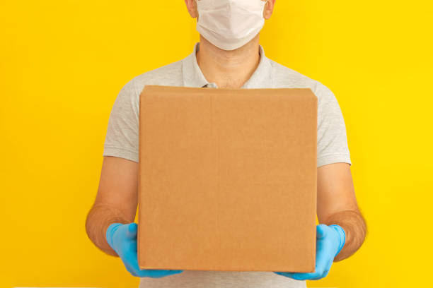 delivery man holding cardboard boxes.delivery by courier in medical rubber gloves on yellow background. the shipping time during coronavirus. quarantine - essential workers stock pictures, royalty-free photos & images