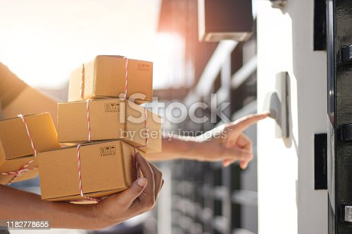 Delivery man holding parcel boxes and ring the doorbell on the client's door in the morning background.