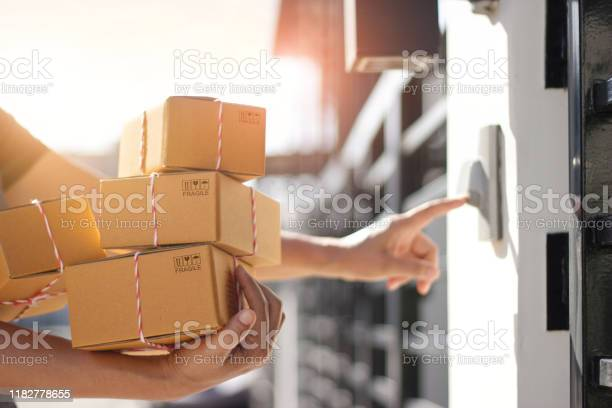Delivery man holding parcel boxes and ring the doorbell on the door picture id1182778655?b=1&k=6&m=1182778655&s=612x612&h=0sgnegn9lvrdroszeeyyjyo ltv3equvew9q1aymlk0=