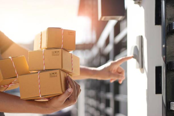 zusteller hält paketboxen und klingeln die türklingel an der tür des kunden im morgenhintergrund. - bekommen stock-fotos und bilder