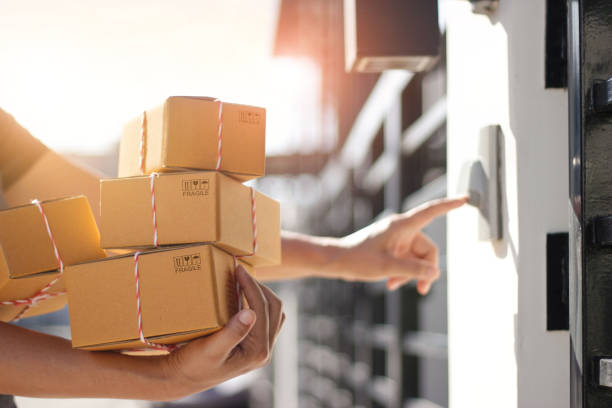 Delivery man holding parcel boxes and ring the doorbell on the client's door in the morning background. Delivery man holding parcel boxes and ring the doorbell on the client's door in the morning background. package stock pictures, royalty-free photos & images