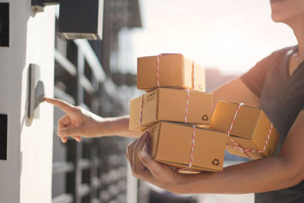 Delivery man holding parcel boxes and ring the doorbell on the customer door in the morning background. stock photo