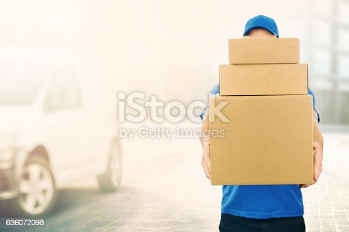 istock delivery man holding pile of cardboard boxes in front 636072098