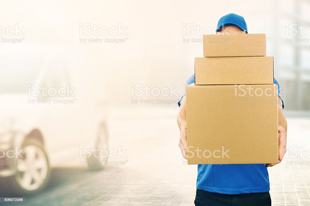 delivery man holding pile of cardboard boxes in front stock photo