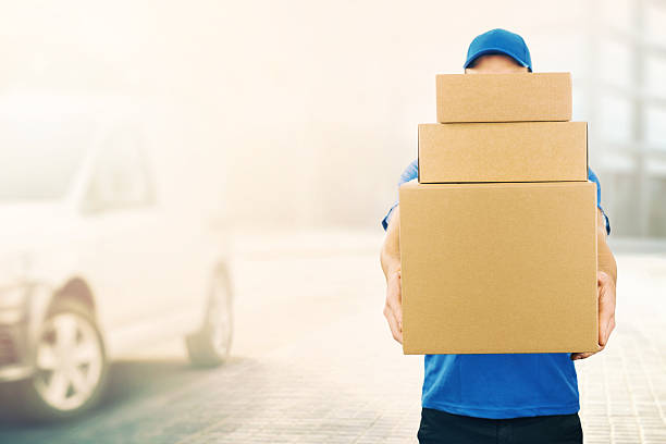 delivery man holding pile of cardboard boxes in front - mail stock photos and pictures