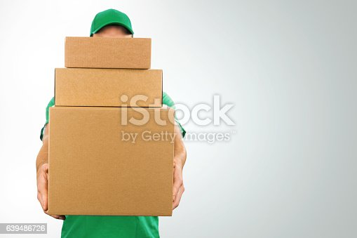 istock delivery man holding pile of cardboard boxes in front 639486726