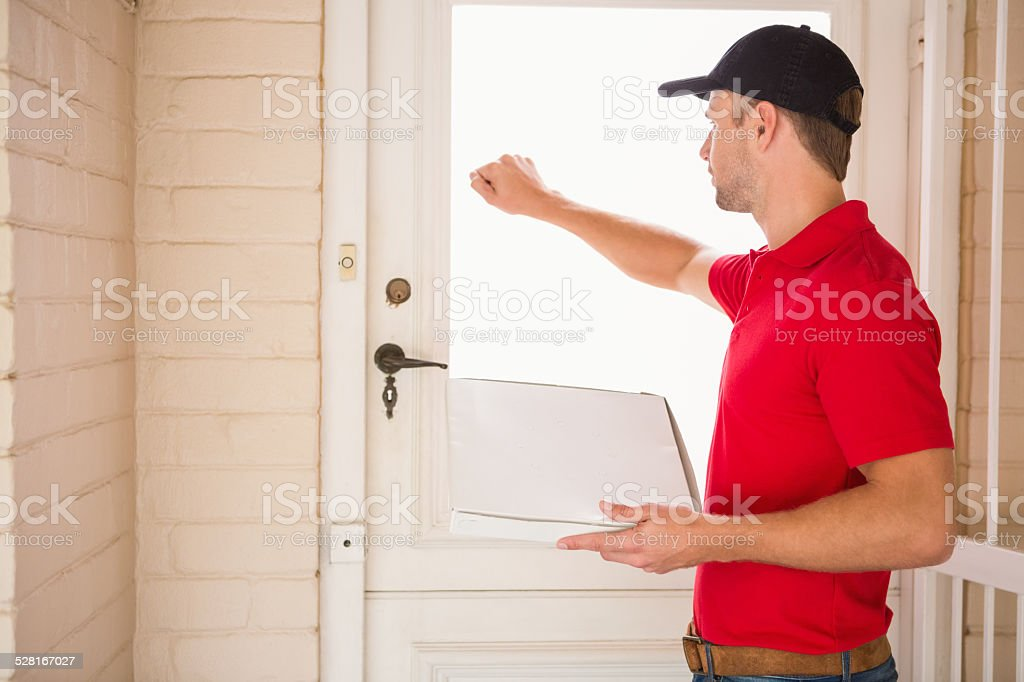 Delivery man holding pizza while knocking on the door stock photo