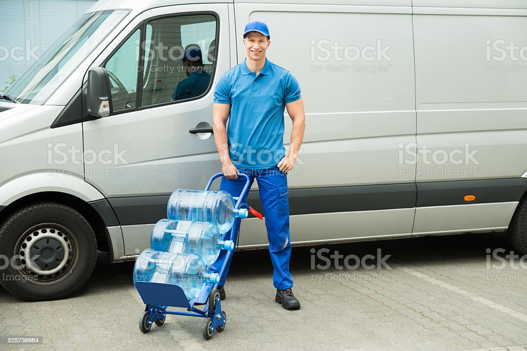 Delivery Man Holding Trolley With Water Bottles stock photo