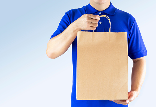 Delivery man in blue uniform and holding paper bag with delivering package on gray background. Concept fast food delivery service or order online shopping and express delivery.