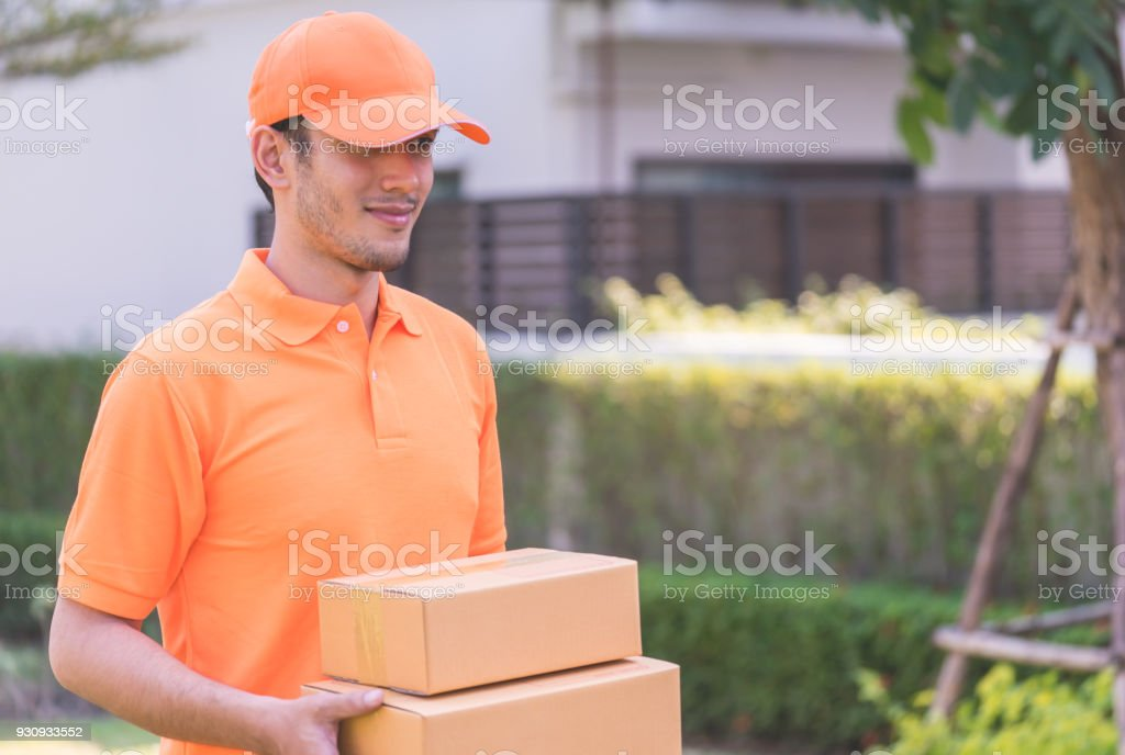 Delivery man in orange bringing in customer the package stock photo