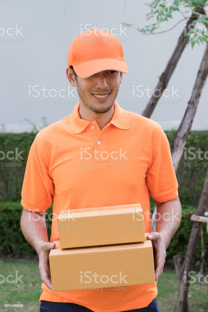 Delivery man in orange bringing package to your home stock photo