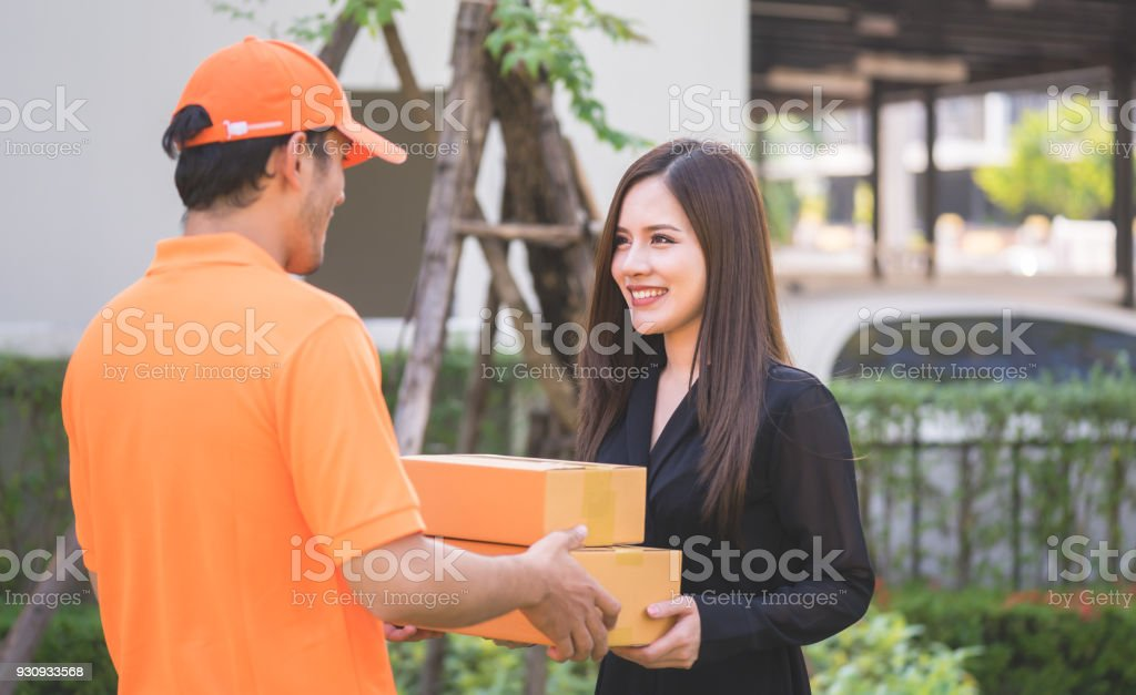 Delivery man in orange bringing woman the package stock photo