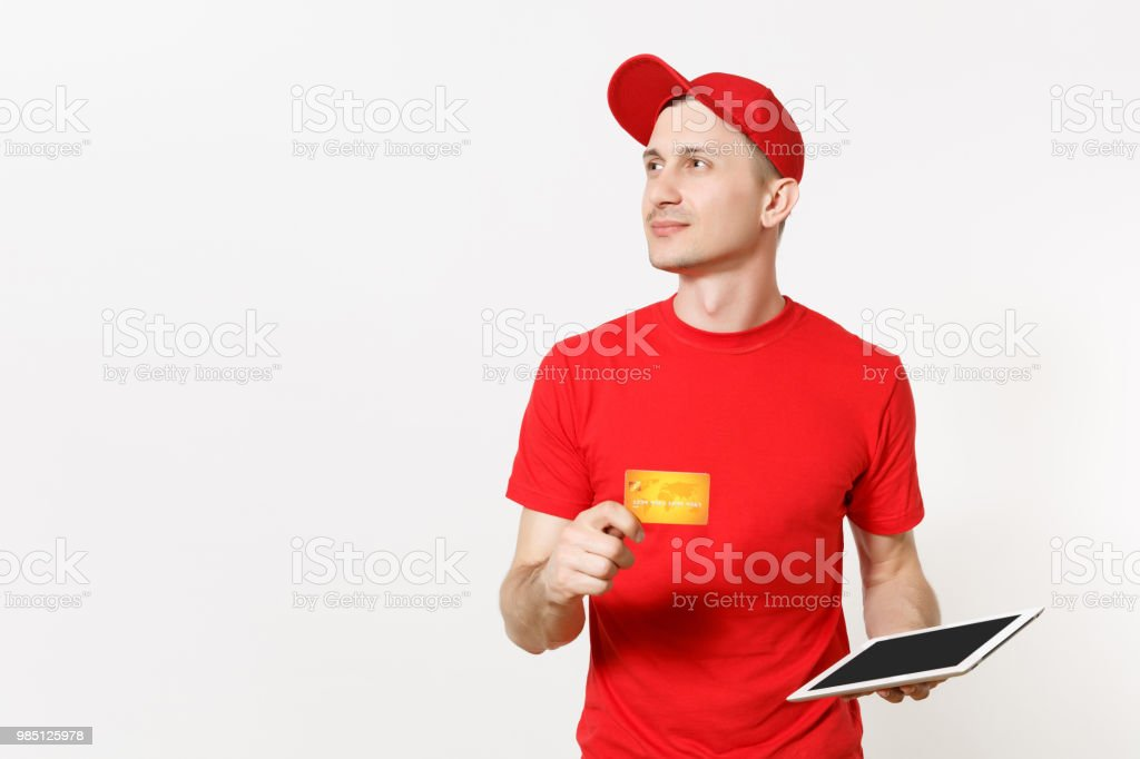 8865c1dd Delivery man in red uniform isolated on white background. Male in cap, t- shirt working as courier or dealer, holding tablet pc computer with blank  empty ...
