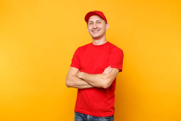 Delivery man in red uniform isolated on yellow orange background. Professional smiling confident male employee in cap, t-shirt courier dealer holding hands crossed folded. Service concept. Copy space. stock photo