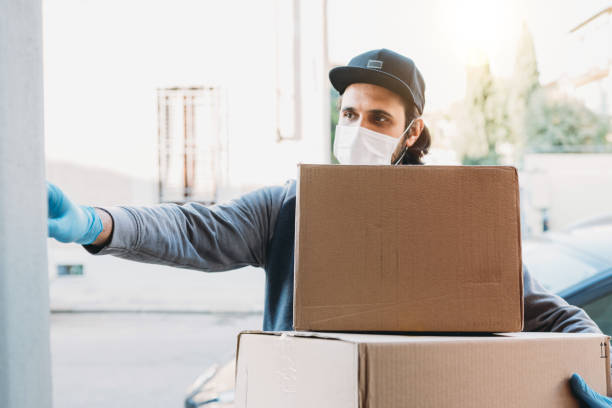 Delivery man is ringing the bell to deliver two cardboard boxes Delivery man is ringing the bell to deliver two cardboard boxes. He's wearing a face mask and protective gloves. delivery man stock pictures, royalty-free photos & images