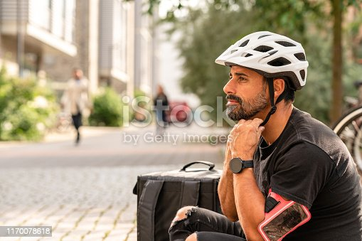 A hispanic man delivering food in the city by riding a bike. Sustainable way of transporting food. He is sitting on the curb drinking coffee.