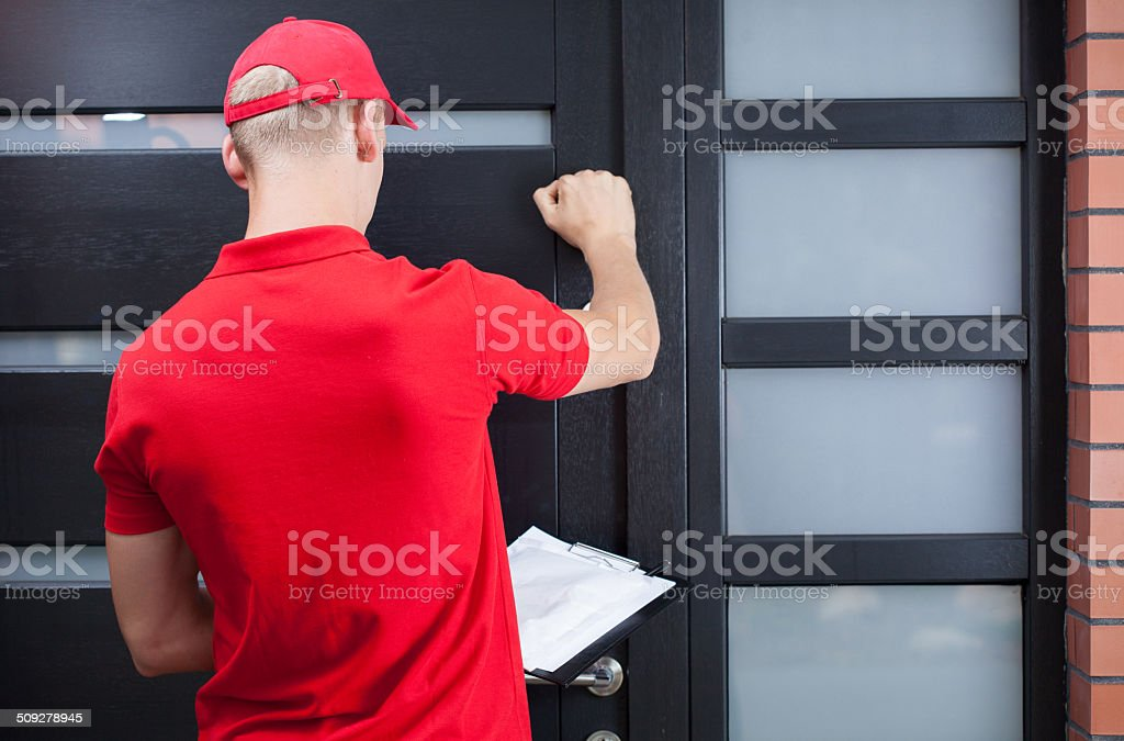 Delivery man knocking on the client's door stock photo