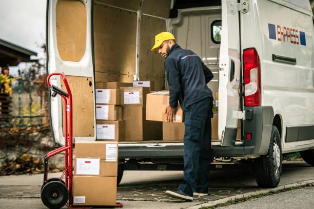 Liefermann lädt Kisten auf einen Schubkarren – Foto
