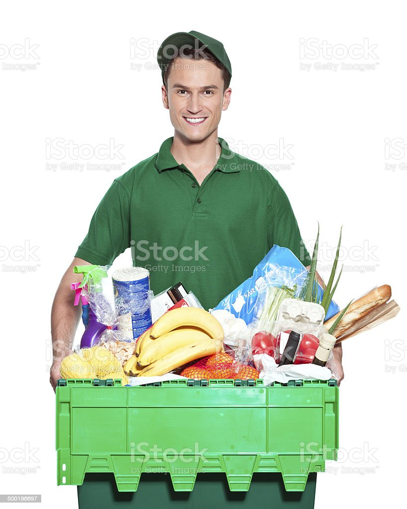 Delivery man Delivery man carrying box with groceries, talking on phone. Studio shot, white background. Adult Stock Photo