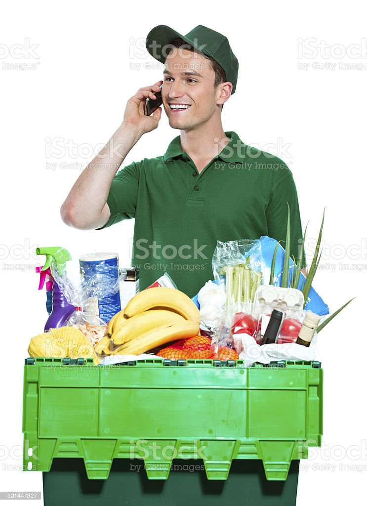 Delivery man Delivery man delivering box with groceries, talking on phone. Studio shot, white background. Adult Stock Photo