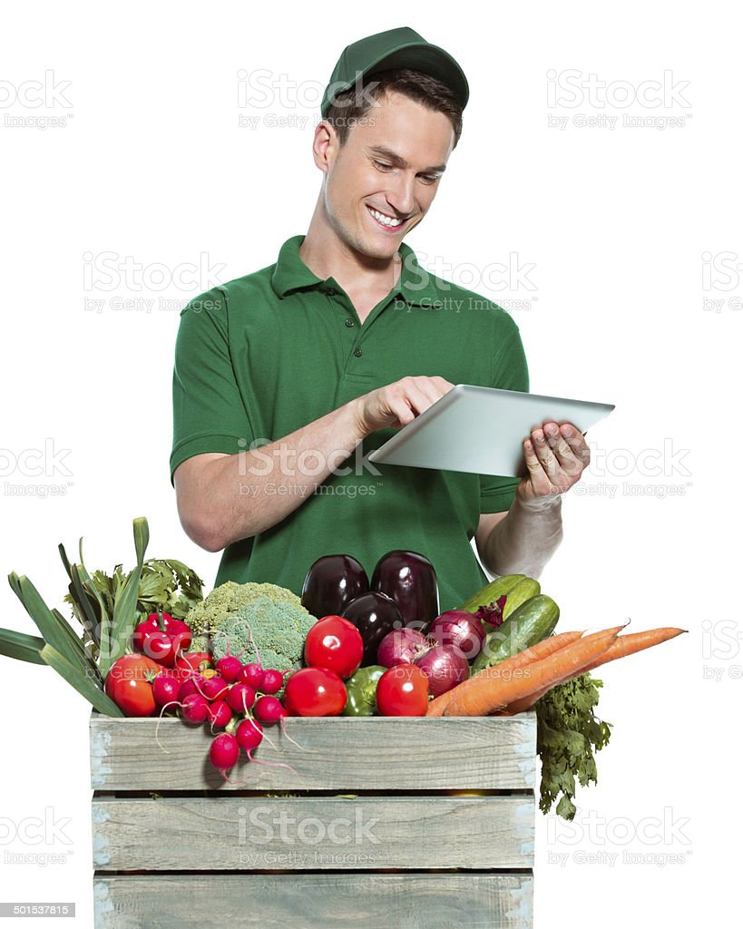 Delivery man Delivery man delivering box with organic food, using digital tablet. Studio shot, white background. Adult Stock Photo