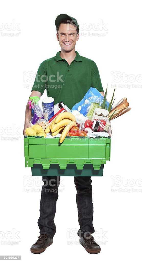 Delivery man Full lenght portrait of delivery man carrying box with groceries. Studio shot, white background. Adult Stock Photo