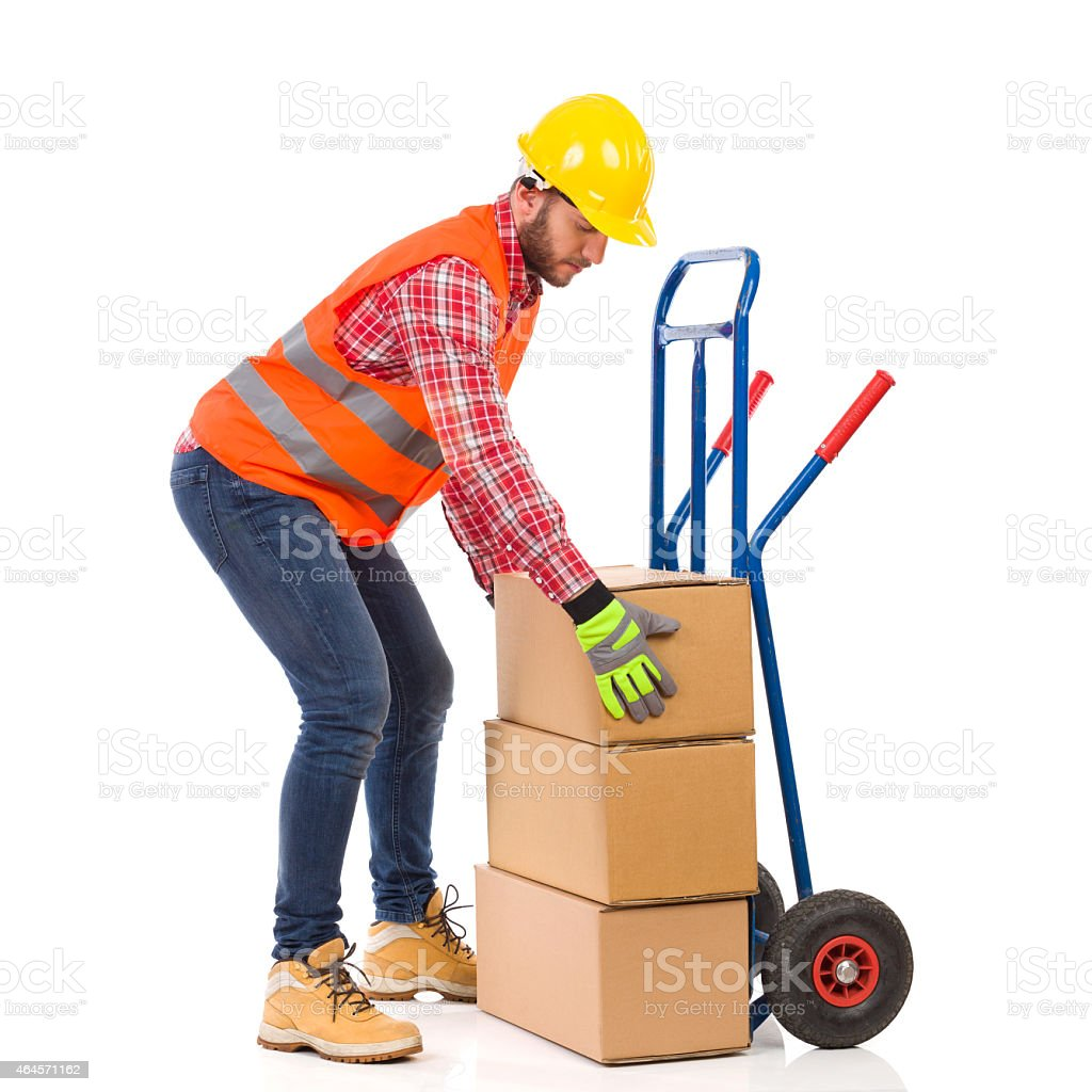 Delivery man place package on delivery cart stock photo