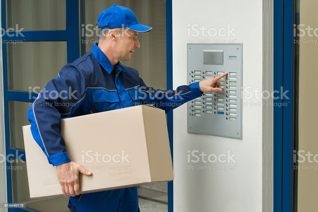 Delivery Man Pressing Button Of Intercom To Enter Building stock photo