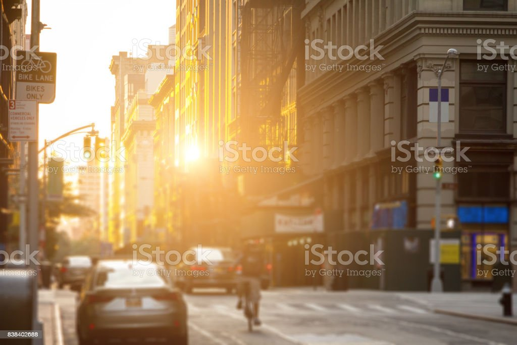 Delivery man rides bike down the streets of New York City with the sunshine reflecting off the downtown building windows stock photo
