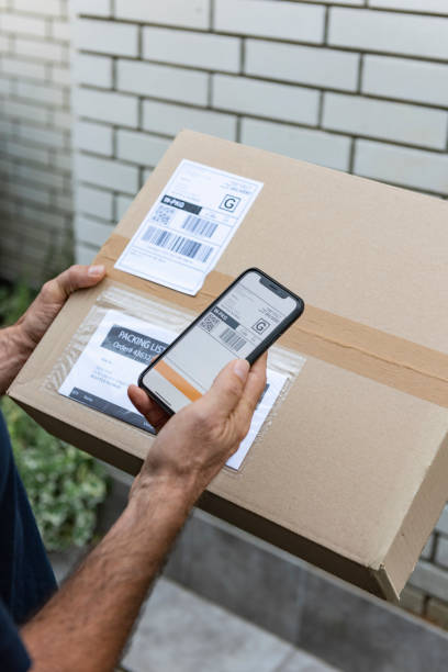 Delivery man scanning barcode on smart phone