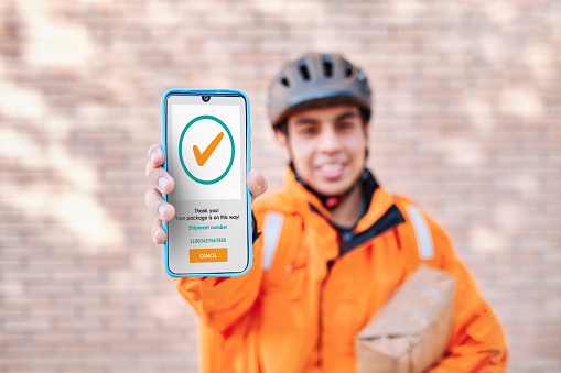 delivery man shows the screen of a phone with the shipment confirmation
