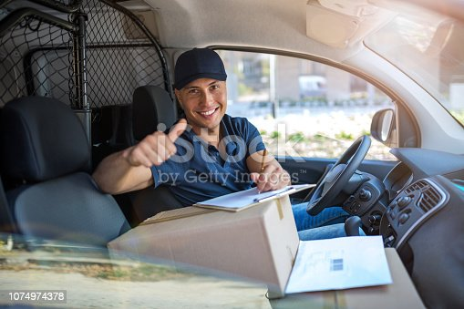 Smiling delivery man sitting with boxes in his van