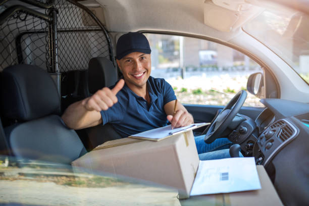 Delivery man sitting in a delivery van Smiling delivery man sitting with boxes in his van delivery man stock pictures, royalty-free photos & images
