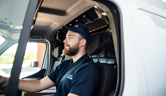 Delivery man sitting in a delivery van