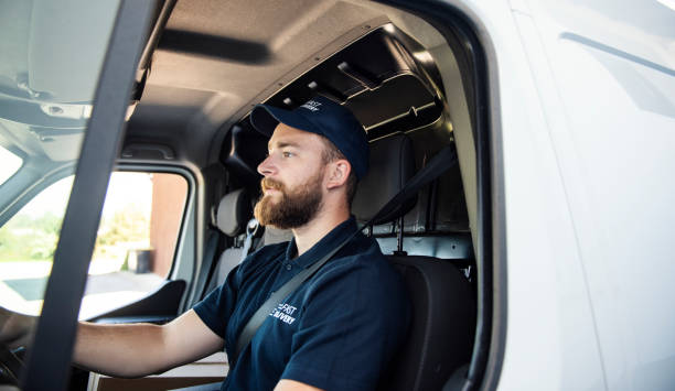 Delivery man sitting in a delivery van Delivery man sitting in a delivery van commercial land vehicle stock pictures, royalty-free photos & images