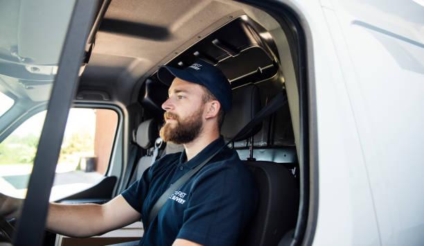 zusteller sitzt in einem lieferwagen - nutzfahrzeug stock-fotos und bilder
