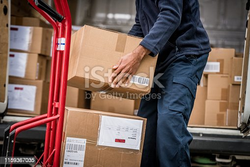 Mid section of delivery man stacking packages from van on cart.